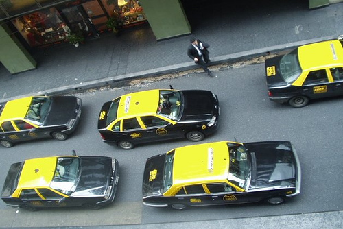 Street filled with taxis and only one potential customer standing on the pavement